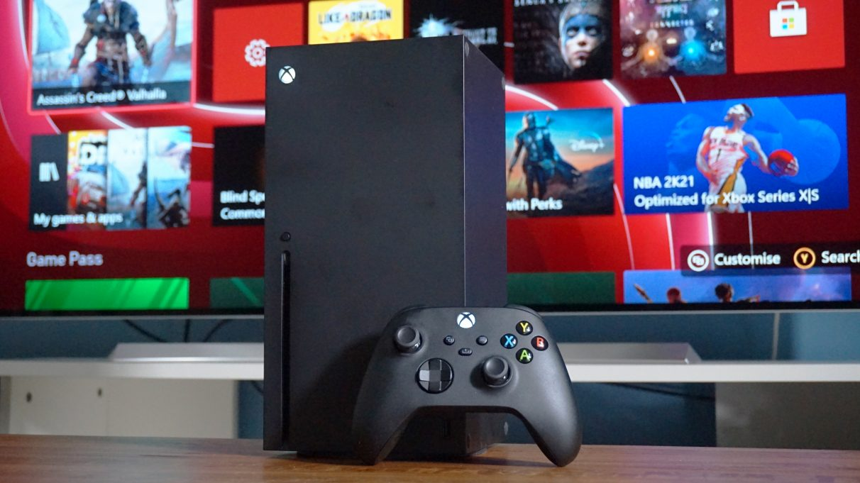 A photo of the Xbox Series X standing upright with its controller in front of a TV.