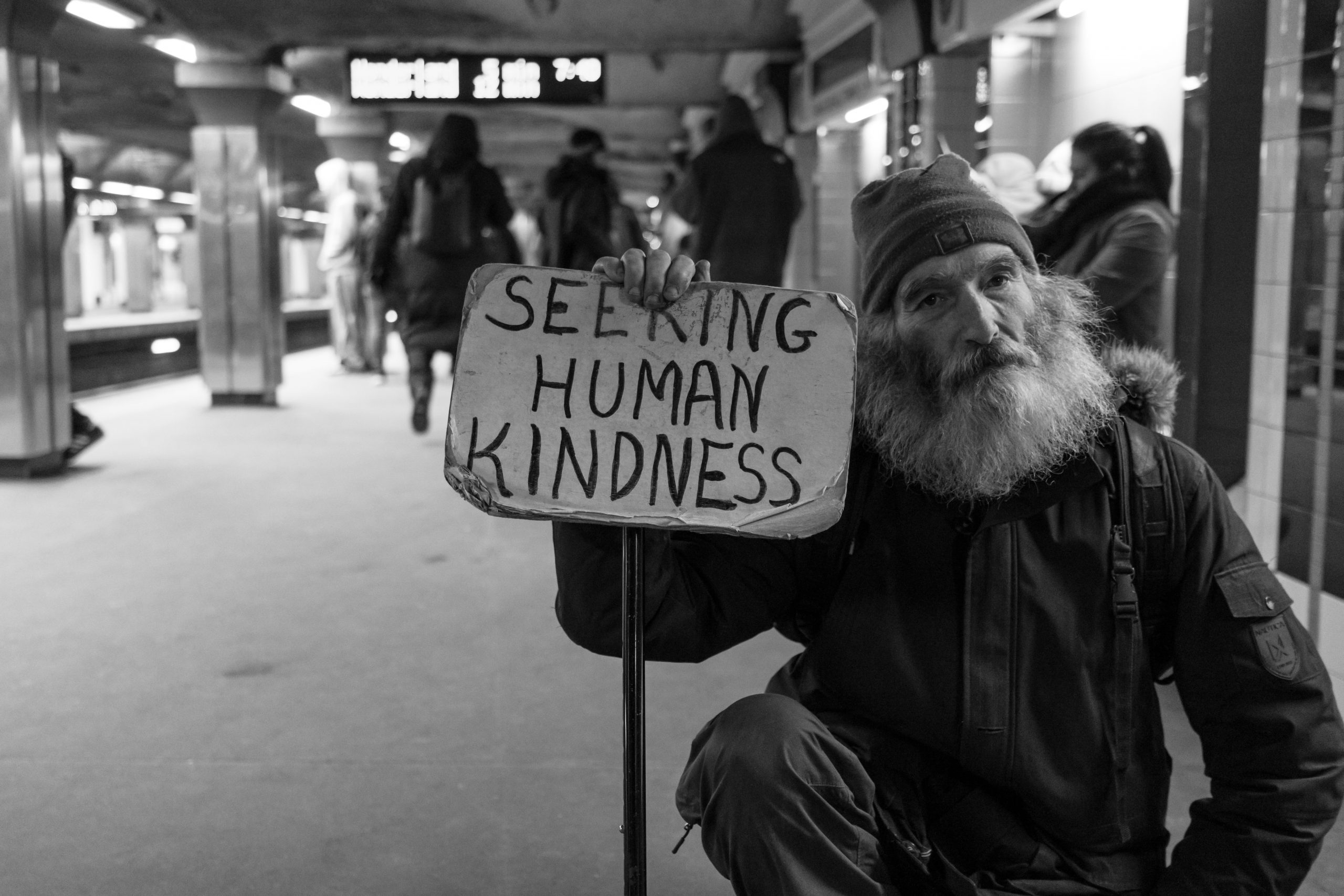 A homeless eprson with a sign that reads 'seeking human kindness'.